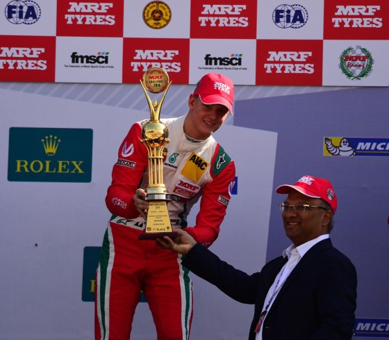 Mick Schumacher receiving the 1st place trophy from Arun Mammen, MD, MRF Tyres on Saturday. An MRF image